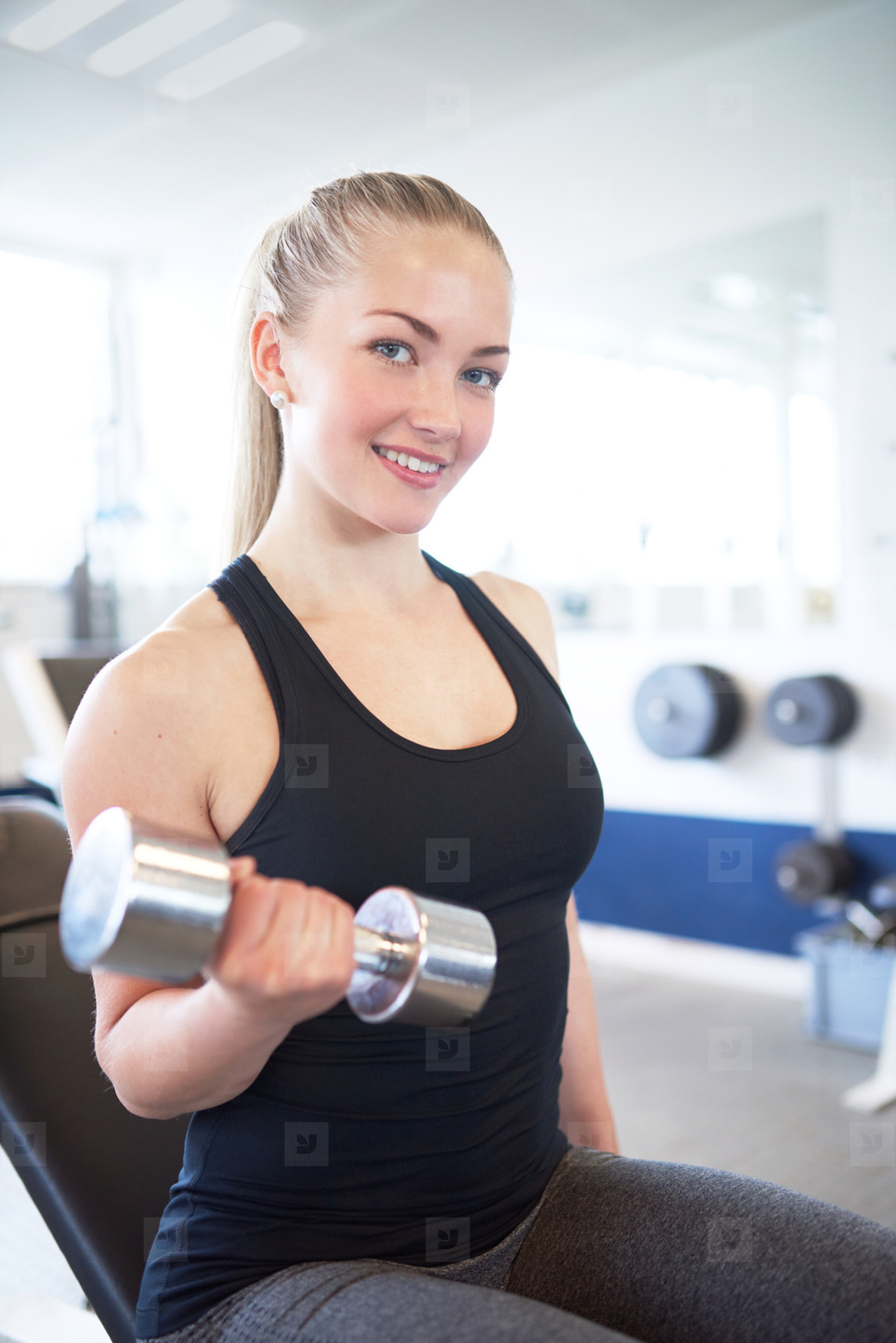 Active Pretty Woman Lifting Weights in the Gym
