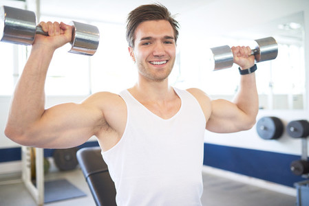 Muscular Man Lifting Two Dumbbells in the Gym