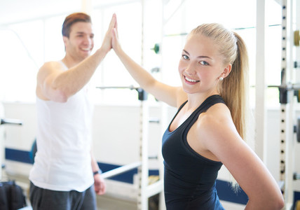 Woman and Man in Gym Celebrating with High Five