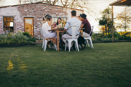 Group of people enjoying summer meal at restaurant