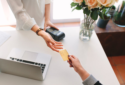 Female florist taking credit card from buyer hand