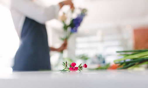 Flower on counter with florist working in background