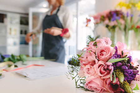 Bouquet in front with florist working in background