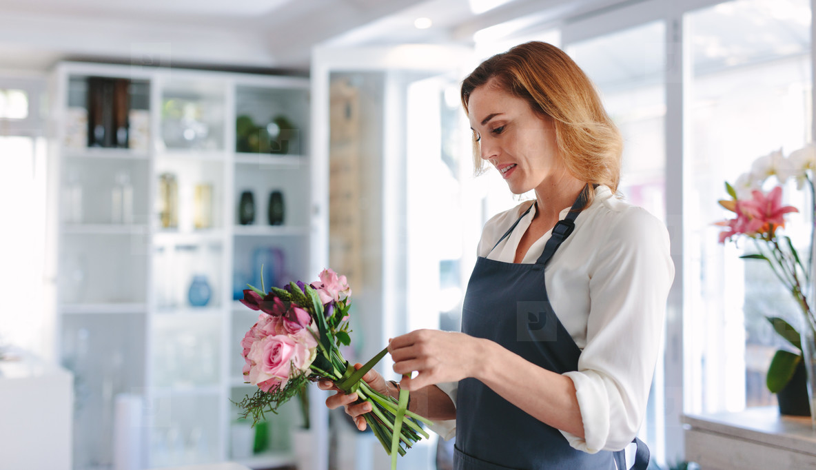 Woman florist preparing a bouquet at her shop
