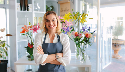 Beautiful woman florist standing in flower shop