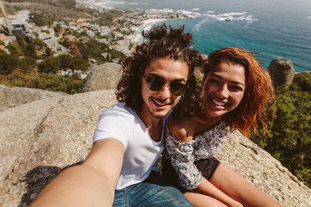 happy couple taking selfie on top of mountain