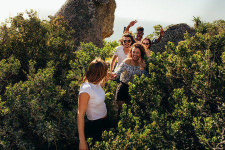 Group of friends walking through a mountain trail