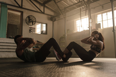 Couple doing sit ups together in gym