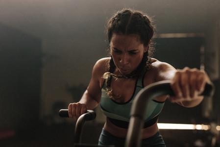 Woman exercising hard on gym bike
