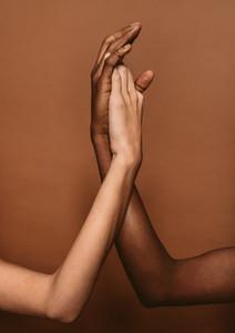 Diverse females putting hands together