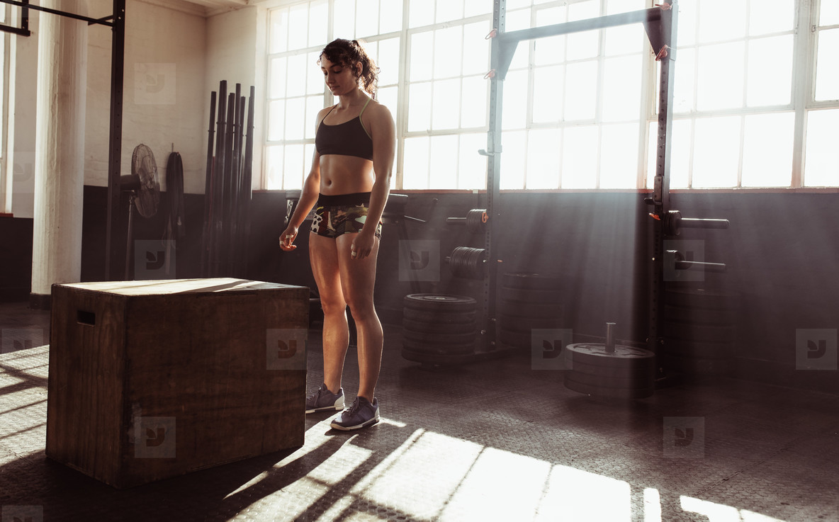 Focused young female athlete working out at gym