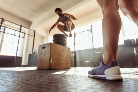 Fit man box jumping at cross training gym