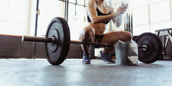 Weightlifter preparing for training with barbells at gym
