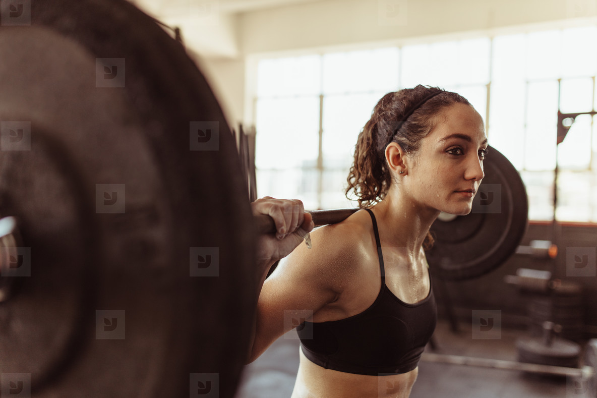 Healthy woman at gym exercising with barbell