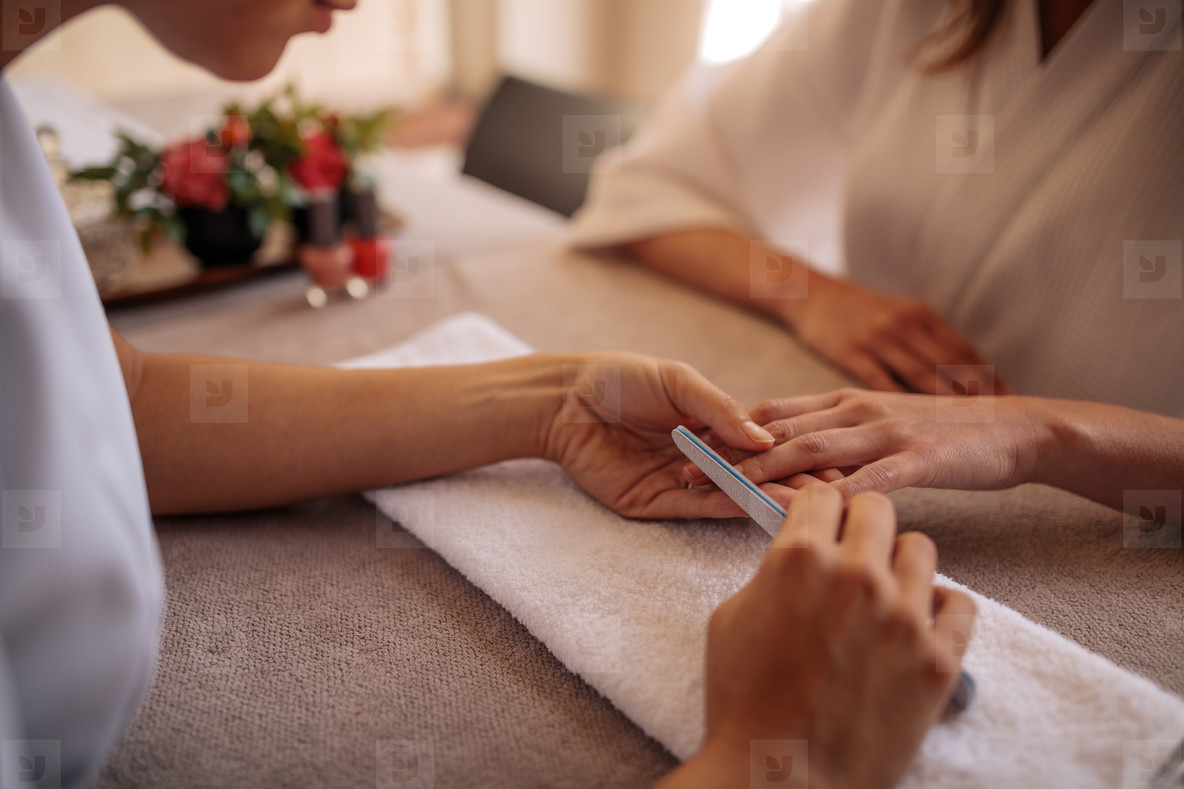 Manicurist shaping nails of client in salon