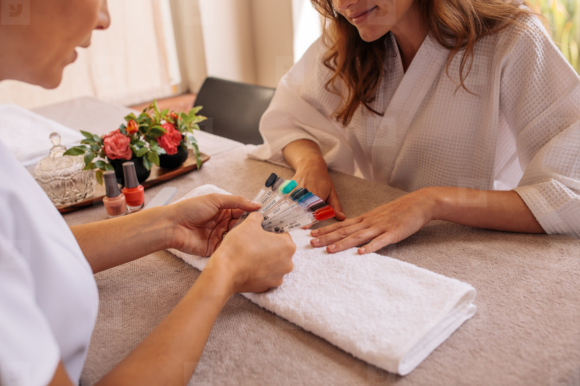Manicurist displaying samples of nail patterns to client