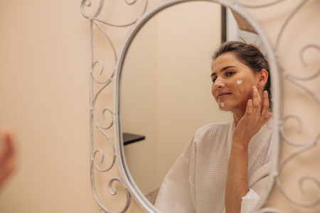 Woman applying moisturizer cream on face