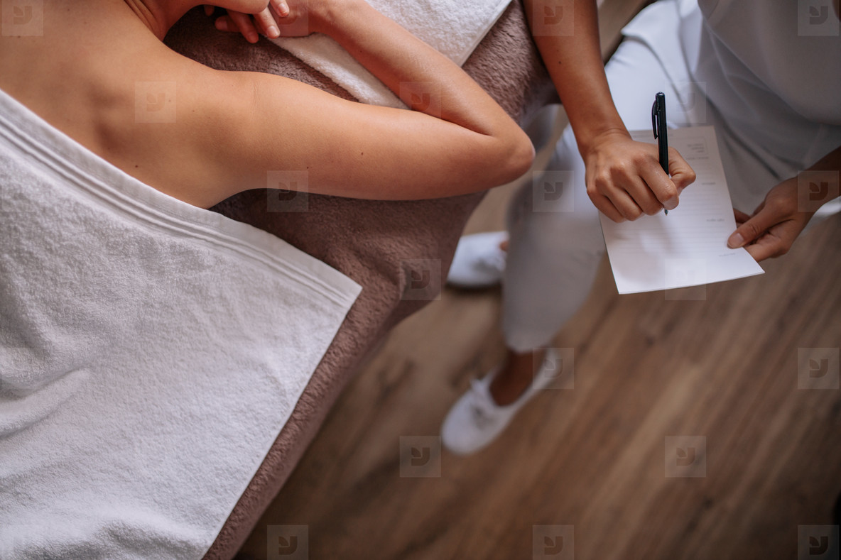 Woman at wellness center with masseuse writing on notepad
