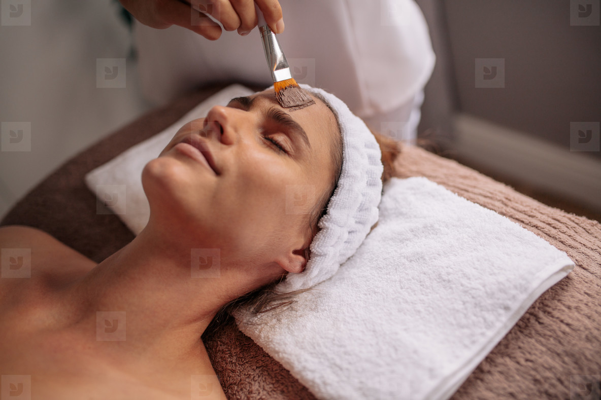 Woman getting facial nourishing mask at spa salon
