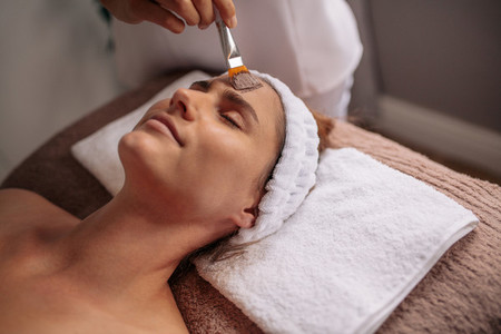 Woman getting facial nourishing mask at spa salon