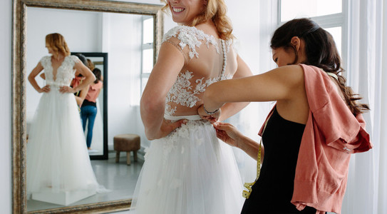 Designer fitting bridal gown to future bride