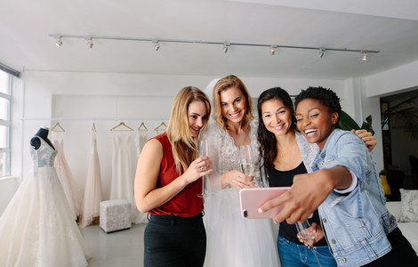 Bride with friends taking selfie in bridal boutique