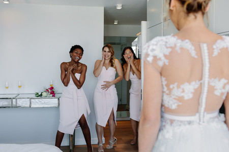 Surprised bridesmaids looking at bride in wedding gown
