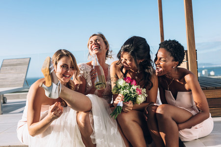 Bride and bridesmaids on rooftop having fun before wedding