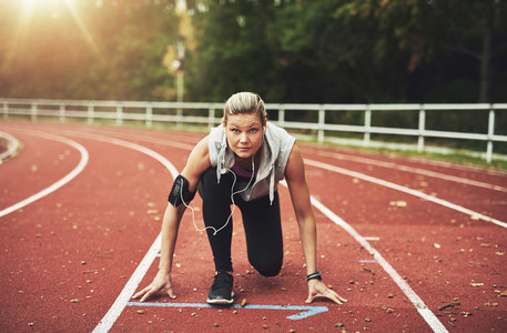 Woman on track field in crouch start position
