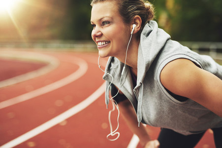 Young blonde woman listening to music and smiling on stadium