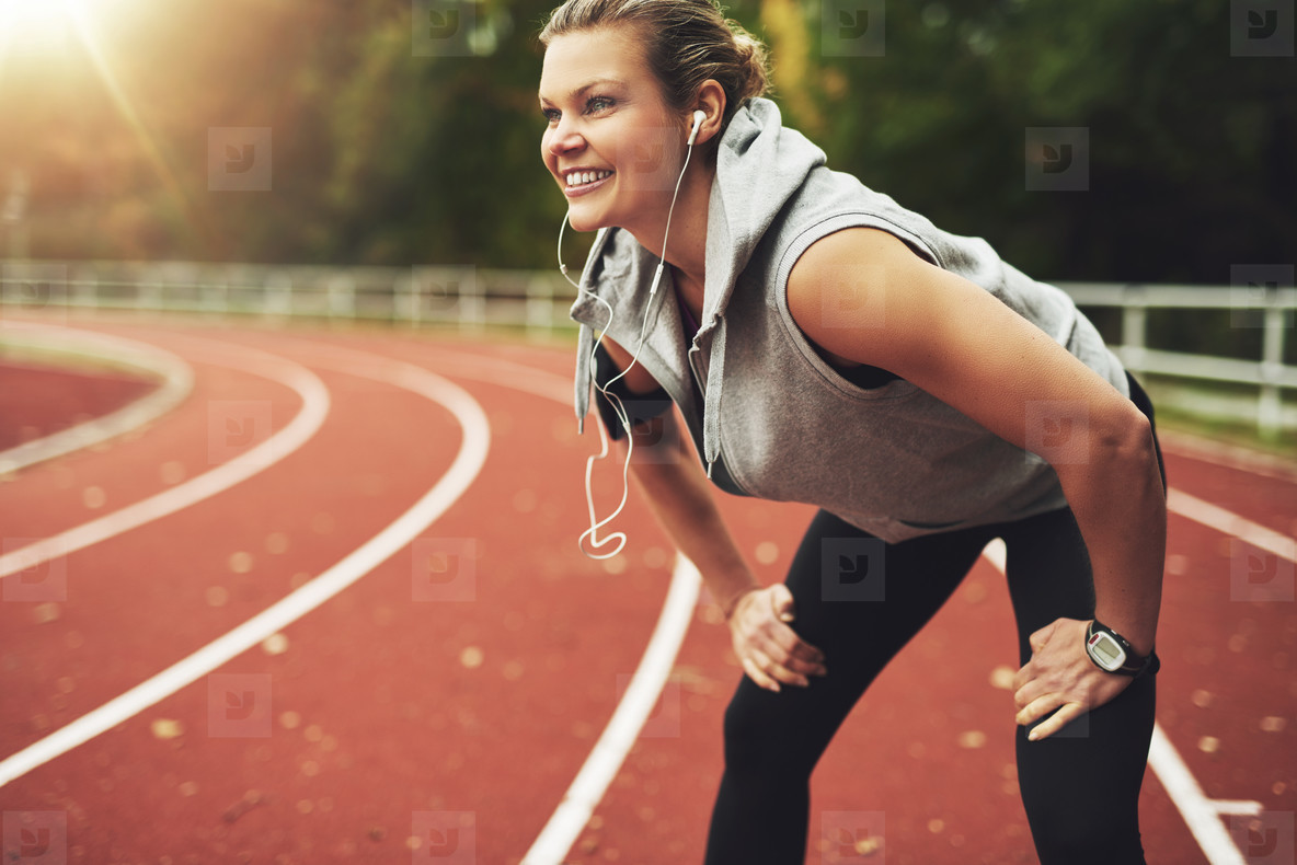 Athletic young woman on stadium smiling and listening to music