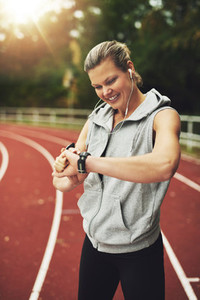 Portrait of blonde athlete looking at her watch