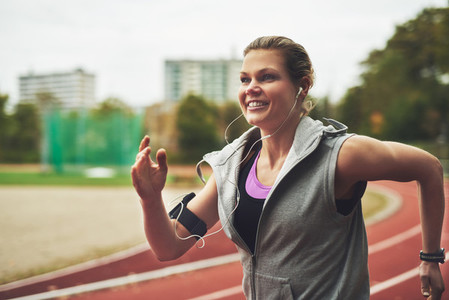 Smiling woman running on track field