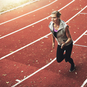 Portrait of young sportswoman running fast on track field