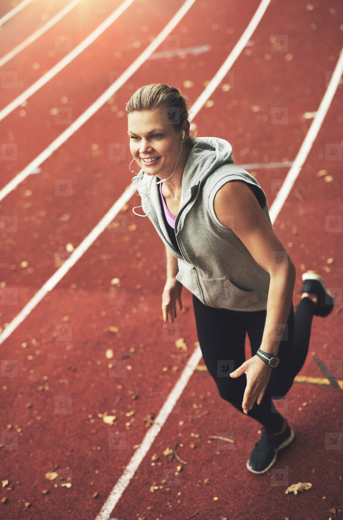 Young female athlete running fast on stadium
