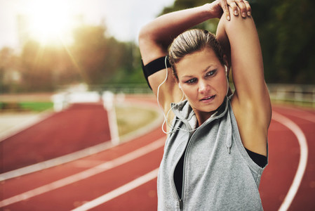 Blonde woman stretching her arms before training