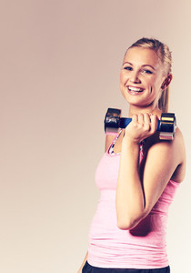 Woman smiling and holding a free weight