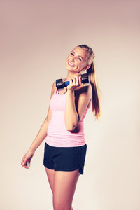 Woman smiling holding a dumbbell