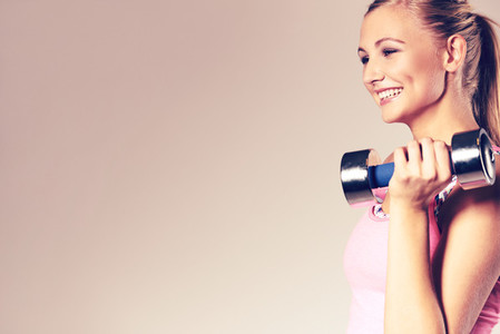Woman smiling and holding dumbbell