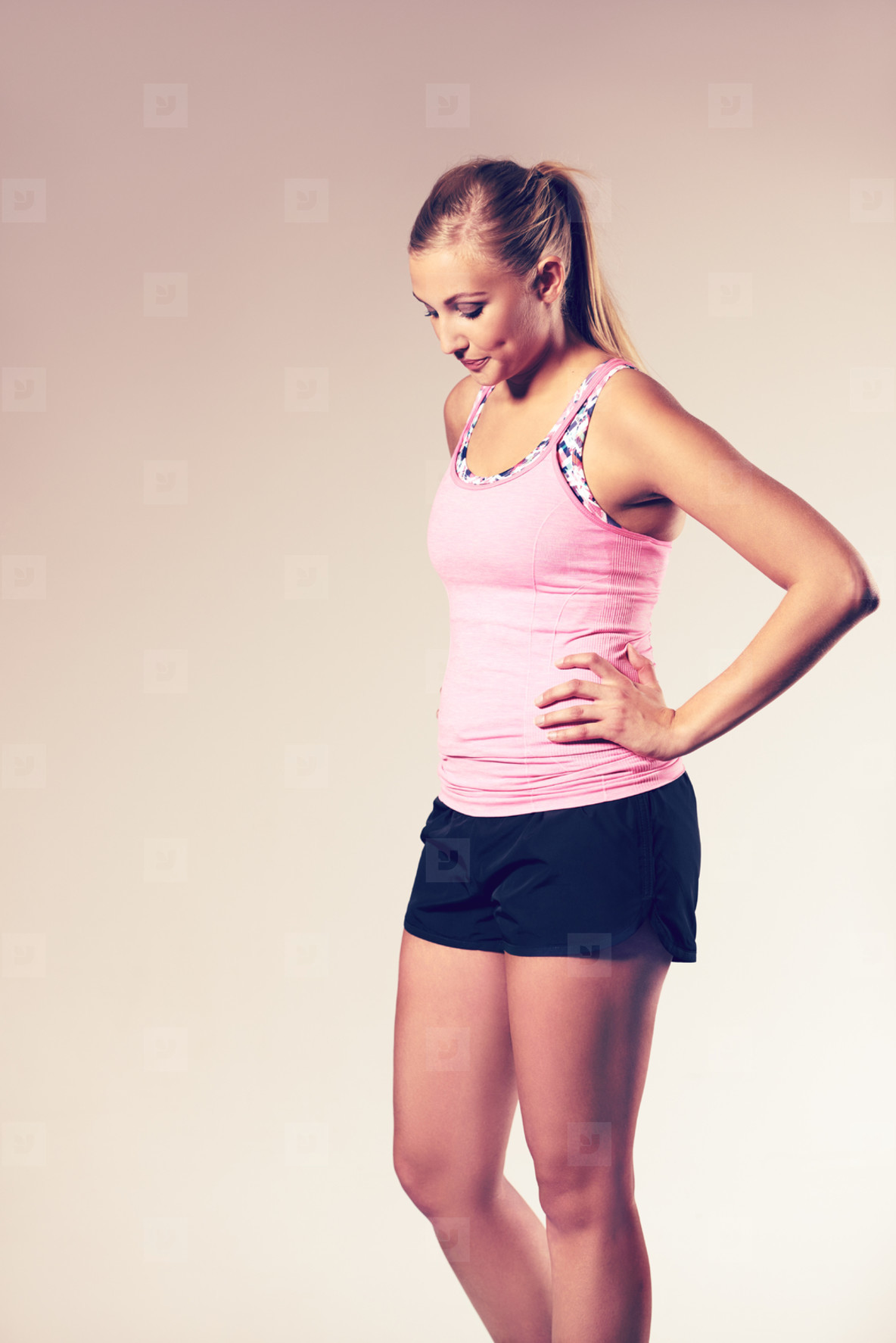 Woman posing in workout clothes looking down