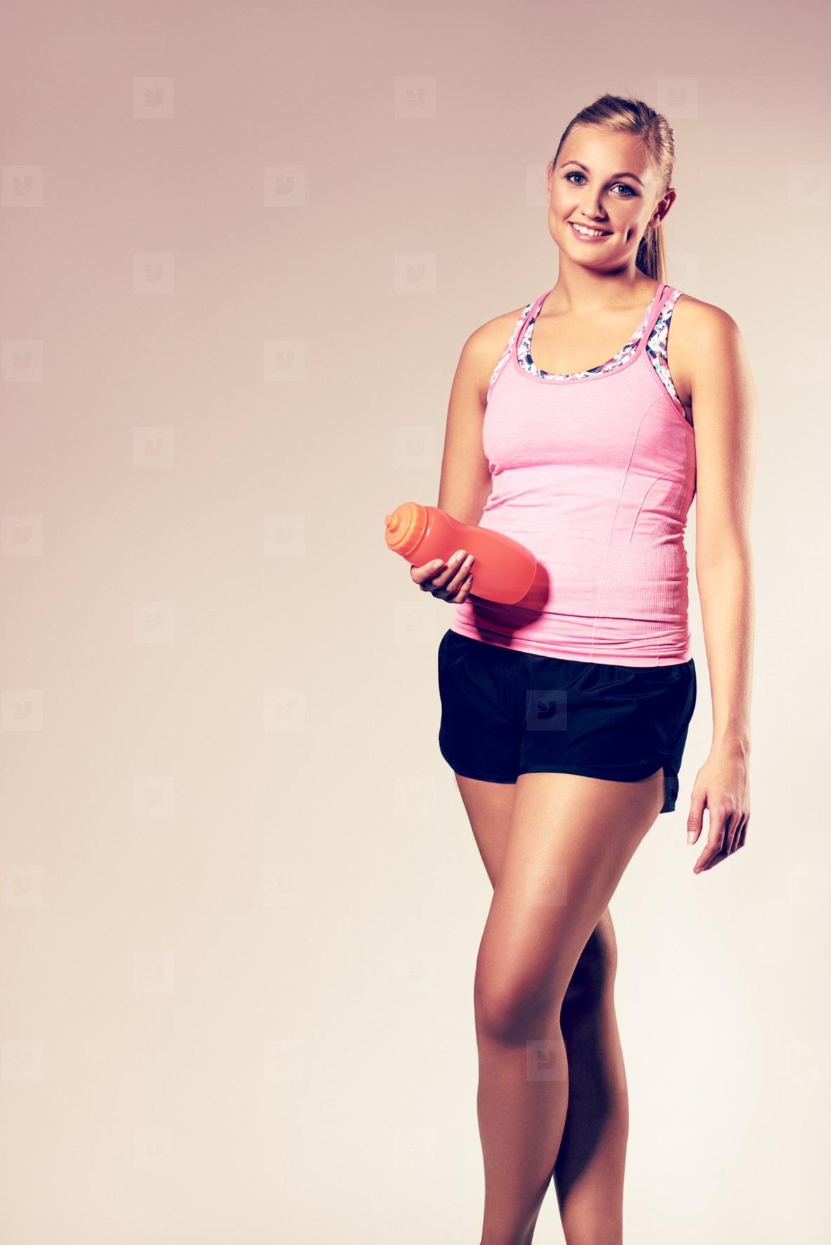 Woman wearing workout clothes holding a water bottle