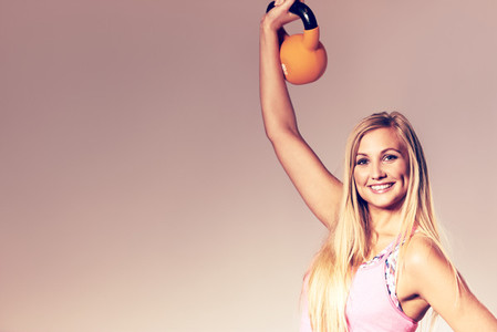 Woman smiling at camera and lifting kettlebell