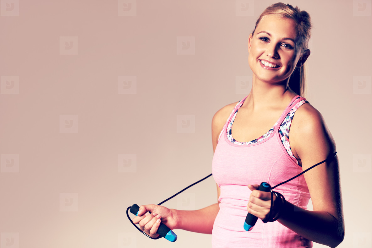 Woman smiling at camera holding a jump rope