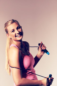 Woman smiling at camera holding a jump rope
