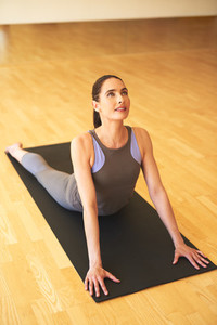 Athletic Woman Stretching her Body on Yoga Mat