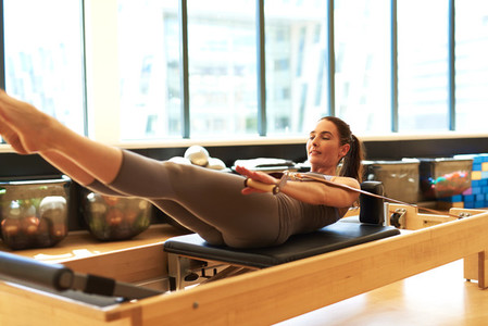 Brunette Woman Practicing Pilates in Studio