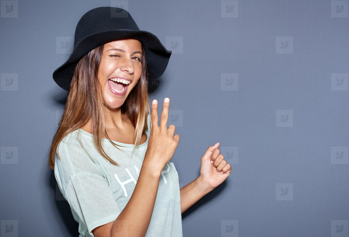 Excited young woman making a V sign gesture