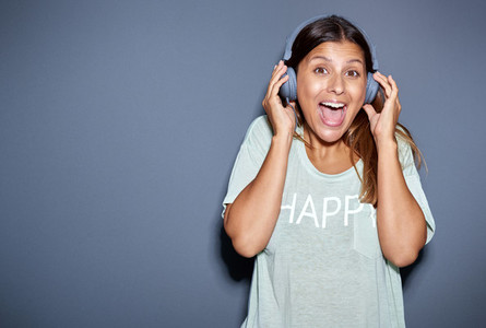 Excited young woman listening to music