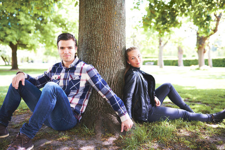 Young couple relaxing in the shade of a tree