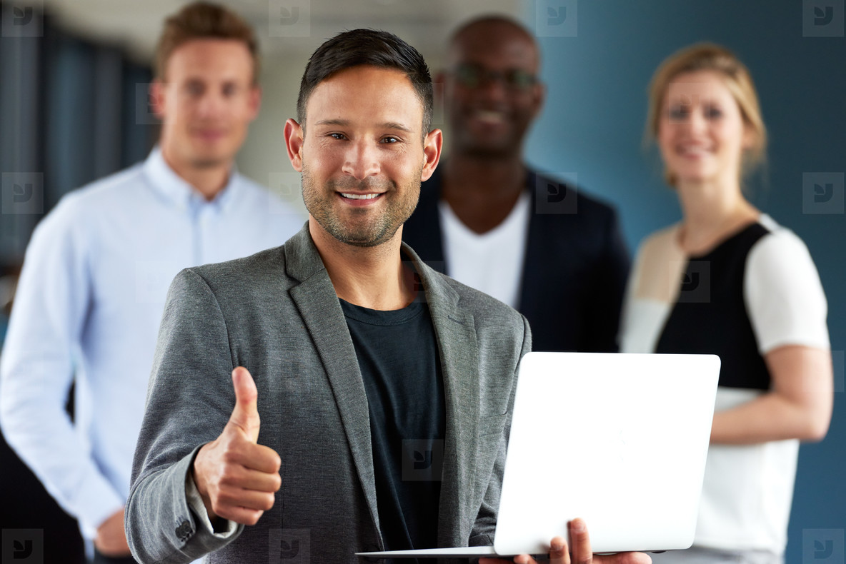 Young white executive making thumbs up sign holding laptop